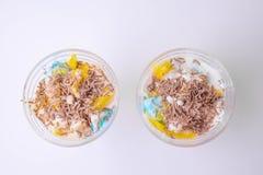 Dessert fait maison savoureux dans un parfait avec la crème glacée colorée, le fruit, les pommes chips de chocolat sur un fond bl image stock