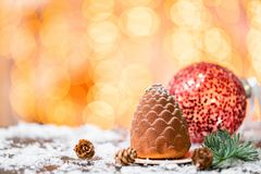 Dessert in the form of Christmas cone. Mini mousse pastry dessert covered with velour. Garland lamps bokeh on background stock photo