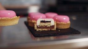 Dessert francese della mousse su una vista del taglio su un fondo vago - il rosa ha lustrato i mini dolci, fine sulla vista Culin stock footage