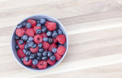 Dessert fresh berries in the bowl. Raspberries and blueberries on a wooden table. Dessert, fresh berries close-up Stock Photo