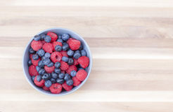 Dessert fresh berries in the bowl. Raspberries and blueberries on a wooden table. Dessert, fresh berries close-up Stock Photography