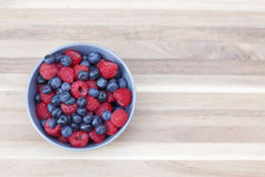 Dessert fresh berries in the bowl. Raspberries and blueberries on a wooden table. Dessert, fresh berries close-up Stock Image