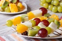 Dessert of fresh fruit on skewers close-up. Horizontal Stock Photos