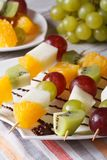 Dessert of fresh fruit on skewers close-up. Vertical Stock Photos