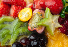 Dessert from fresh fruits and berries (macro). Macro of mixed fruits and berries in gel (raspberry, strawberry, red and white grapes, kiwi, clementines Stock Photography