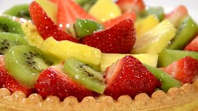 A dessert. Fruit tart on red plate rotating. close up stock video
