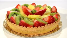 A dessert. Fruit tart on red plate rotating. stock footage