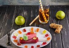 Dessert - gelato nella forma e nel gusto dell'anguria e con il gusto delle ciliege, dei dolci, delle mele e di un vetro di succo  immagini stock