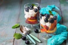 Dessert in glas-gestremde melk room met bosbessen en perzik op een rustieke groene lijst Selectieve nadruk Lepels, turkoois serve stock foto