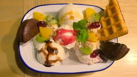 Dessert with ice cream, cookies, waffles and fruit in white plate, closeup view. Sweet dessert with ice cream, cookies, waffles and fruits in a white plate in stock footage