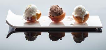 Dessert ice cream on peach. Dark background with reflection Stock Images