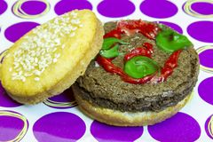 Dessert impostor hamburger on sesame seed bun with pickles and k Stock Photography