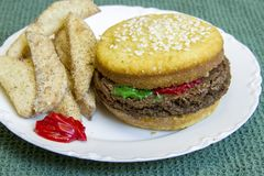 Dessert impostor hamburger and fries. Dessert impostor mock cheeseburger with vanilla cupcake bun and brownie burger on white china plate with mock apple fries Royalty Free Stock Image