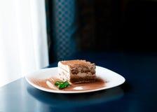 Dessert italiano tradizionale di tiramisù sul piatto bianco sulla tavola blu scuro accanto alla finestra del roon con le tende Co fotografia stock