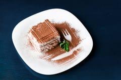 Dessert italien traditionnel de tiramisu du plat blanc sur la table bleu-foncé Fermez-vous vers le haut de la nourriture de vue s photo stock