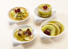 Dessert kiwi and red berries in jelly. Four small plates filled with pieces of kiwi and red berries in jelly Royalty Free Stock Images
