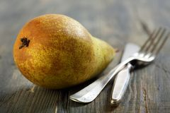 Dessert knife, fork and ripe pear. Stock Photo