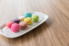 Dessert Macaroon placed in a dish with a wooden background. Stock Photo