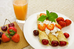 Dessert made from pancakes stuffed with curd cheese with strawberries and cherries is on a table in a white plate. Pancakes stuffed with cottage cheese with royalty free stock image