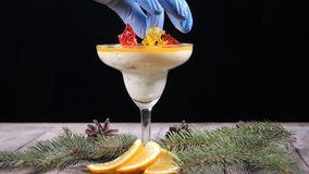 Dessert making concept. Delicious dessert in glass bowl on wooden board decorated with fir-tree branches and slices of. Lemon. Isolated on black background stock video