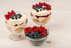 Dessert with mascarpone, cream, and berries in the glass cups on the wooden background. Dessert with mascarpone, cream, and berries in the glass cups on the Stock Images
