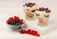 Dessert with mascarpone, cream, and berries in the glass cups on the wooden background. Dessert with mascarpone, cream, and berries in the glass cups on the Royalty Free Stock Photography