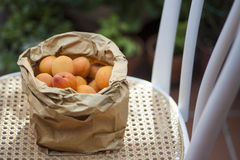 Paper Bag of Peaches on Wicker Chair Stock Photography