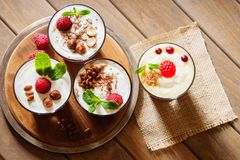 Dessert met bessen, gelei, room, noten en muntblad op een scherpe houten raad Royalty-vrije Stock Foto's