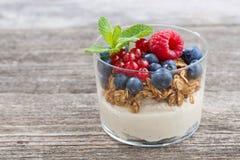 Dessert with milk cream, muesli and berries on wooden table. Closeup Stock Photo