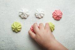 Dessert multicolori dell'aria della meringa su un fondo, su una gioia e su una celebrazione d'annata bianchi La mano di un bambin fotografia stock