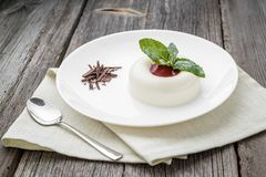 Dessert named panacota. With chocolate and jam. On a wooden table royalty free stock image