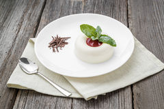Dessert named panacota. With chocolate and jam. On a wooden table royalty free stock photography