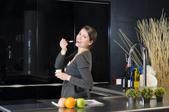 Dessert in New Kitchen. Beautiful woman enjoying new kitchen Royalty Free Stock Photography