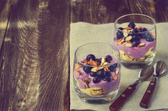 Dessert of oatmeal, banana, yogurt, blueberries and almond. In glass bowls on rustic wooden background. Vintage toned picture Stock Photos