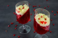 Dessert panakota and red jelly and pomegranate seeds. On rustic wooden table royalty free stock image