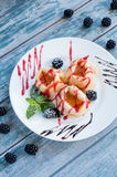 Crepes with jam and blackberries. The sweet crepes with jam and blackberries. On a white plate. Summer dessert on a blue background, which is stylized as old Royalty Free Stock Photos