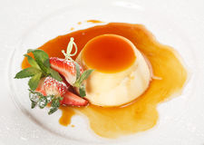 Dessert panna cotta. On white plate decorated with strawbery, mint and caramel royalty free stock photo