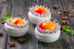Fruit mousse cake with a mango and litchi decor on a wooden stand stock photos