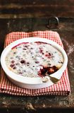 Dessert pie with mixed berries - cherry, cranberry - dusted with icing sugar in a baking dish on a wooden table, selective focus. stock images