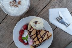 Dessert plate of crepe with strawberry, banana, and ice cream on wooden table. royalty free stock photography