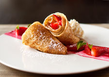 A dessert plate with crepes, strawberry fruits, whipped cream and mint Stock Image