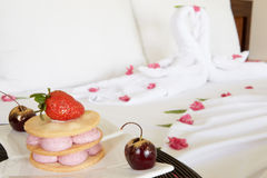 Dessert On Plate Next To Decorated Hotel Bed Royalty Free Stock Photos