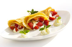 A dessert plate with pancakes, strawberry, whipped cream and mint Stock Images