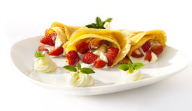 A dessert plate with pancakes, strawberry, whipped cream and mint Stock Image