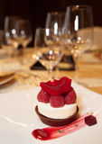 Dessert on plate in restaurant. With wineglasses in blurred  background Royalty Free Stock Images