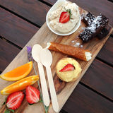 Dessert platter on wooden board with brownies, tart, fruit, bran Stock Photo