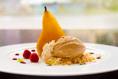 Dessert with poached pear, ice cream, whipped cream, fruits Stock Photos