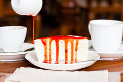 Dessert - pour red syrup on cheese cake. On white dish, on wood table in coffee shop, side view Royalty Free Stock Images