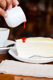 Dessert - pour red syrup on cheese cake. On white dish, on wood table in coffee shop, side view Stock Photos