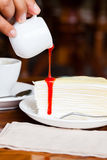 Dessert - pour red syrup on cheese cake. On white dish, on wood table in coffee shop, side view stock photography